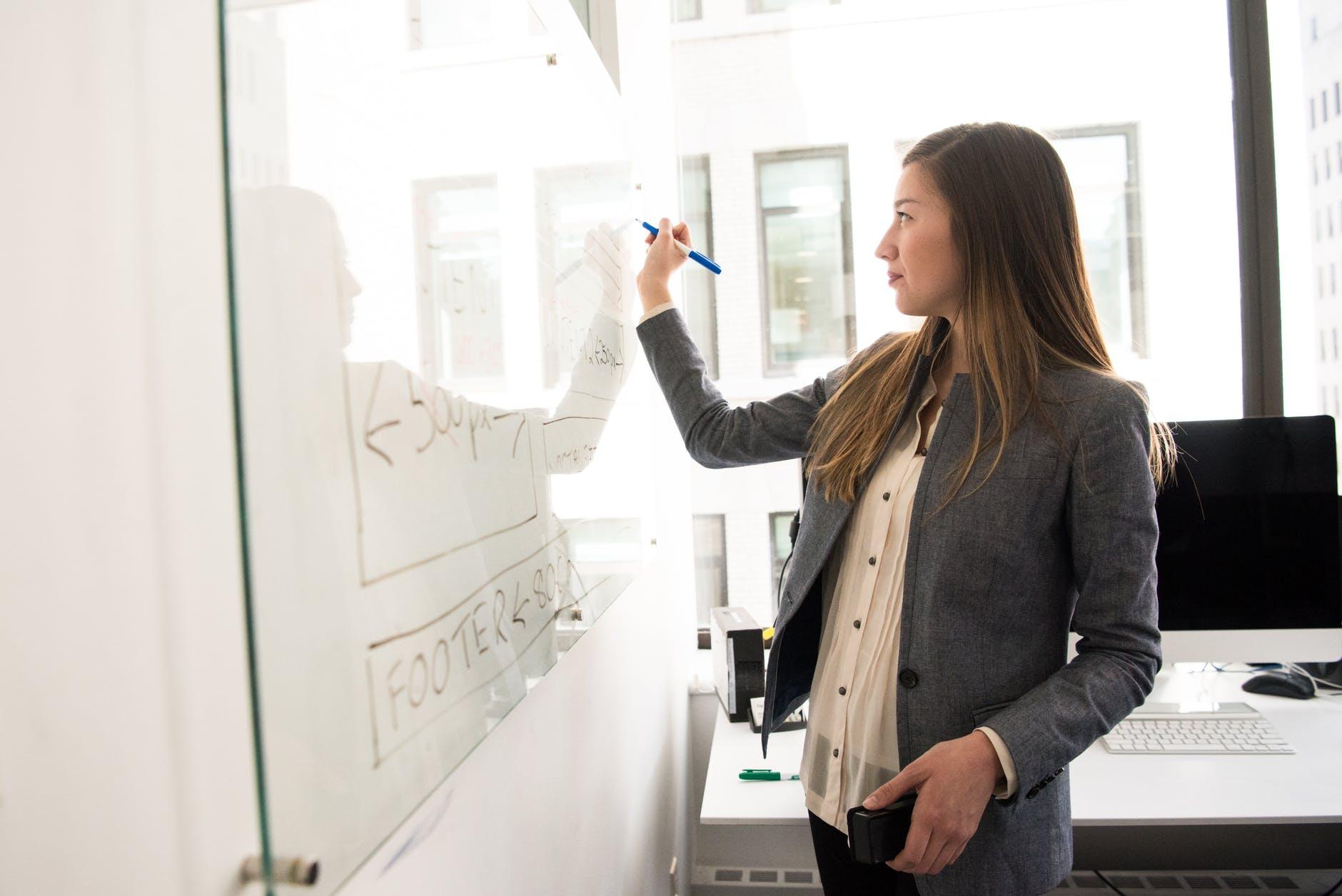 woman wearing gray blazer writing on dry erase board